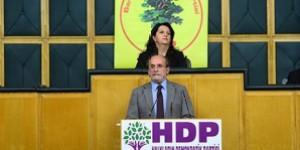 HDP co-leader Ertugrul Kückcü speaks, above him sits BDP MP Pervin Buldan, at hte ceremony in Ankara where the BDP MP's joined the HDP.