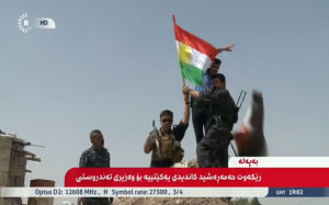 Kurdish fighters place their flag in formerly disputed city Kirkuk, Iraq.