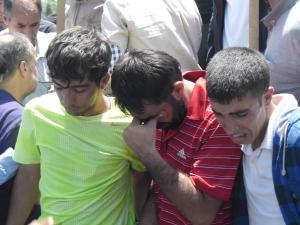 Three friends of Ramazan Baran mourn at their friend's grave.