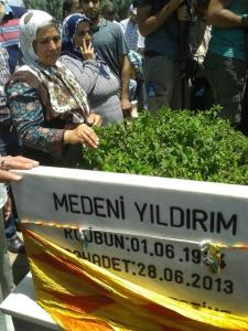 The mother of Medeni Yildirim next to her son's grave, during the funeral of Ramazan Baran.